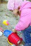 The small girl in pink clothes plays sand Royalty Free Stock Photography