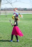 Little girl in pink swings at a pinata with a wood baseball bat. Small girl in pink holds a wood baseball bat and  swings at a colorful pinata hanging from a Stock Images
