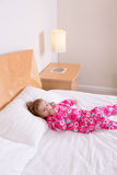 Small girl in pink pajamas lying resting on a bed Royalty Free Stock Image