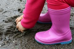 Small girl in pink rubber boots grabs wet mud from puddle Stock Image
