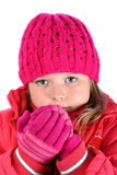 Small girl in pink sweater breathing on her hands Royalty Free Stock Photography