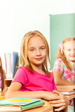 Small girl in pink tshirt sits at desk and looks Royalty Free Stock Photo
