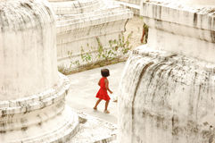 Small Girl Playing Hide and Seek at Buddhist Temple. A small Thai girl runs around a Buddhist temple playing hide and seek with her 2 sisters Stock Photography