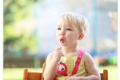 Small girl playing indoors eating candy Stock Photo