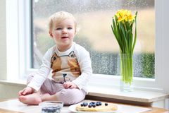 Small girl playing indoors eating tasty pancakes. Cheerful little toddler girl eating delicious pancakes with blueberries sitting in the kitchen on a rainy day Royalty Free Stock Photo