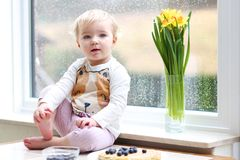 Small girl playing indoors eating tasty pancakes. Cheerful little toddler girl eating delicious pancakes with blueberries sitting in the kitchen on a rainy day Stock Photo