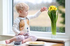 Small girl playing indoors eating tasty pancakes. Cheerful little toddler girl eating delicious pancakes with blueberries sitting in the kitchen on a rainy day Stock Photos