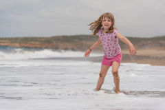Small girl playing in sea waves stock images
