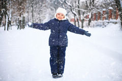 Small girl playing with snow in a park. The concept of childhood and the winter season. Small girl playing with snow in a park. Wonderful snowy day. The concept Royalty Free Stock Photos