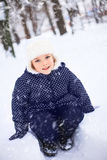 Small girl playing with snow in a park. The concept of childhood and the winter season. Stock Image