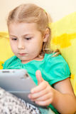Small girl playing with the tablet pc Stock Photos