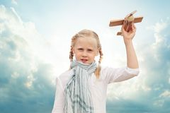 Small girl playing with a toy airplane against the blue sky stock photos