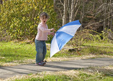 Small girl playing with umbrella on windy day. Stock Photo