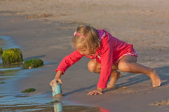 Small girl plays on the beach Royalty Free Stock Photography