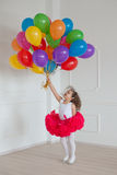 Small girl plays with colorful balloons Stock Image