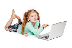 Small Girl Pointing At Laptop Computer. Young girl with laptop. Isolated on white background. Smiling and pointing at laptop computer Stock Photos