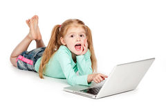 Small Girl Pointing At Laptop Computer. Young girl with laptop. Isolated on white background. Smiling and pointing at laptop computer Royalty Free Stock Image
