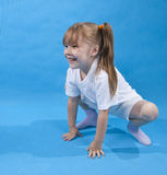 Small girl is posing as frog on blue Stock Images