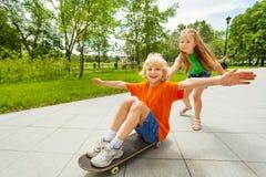 Small girl pushing happy boy on skateboard royalty free stock photo