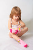 Small girl is puting on the socks Stock Photo