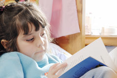 Small Girl reading. Close up of a small girl reading a book stock images