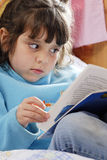 Small Girl reading. Close up of a small girl reading a book stock photography