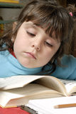 Small girl reading. Over a table royalty free stock images