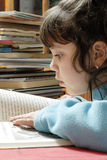 Small girl reading. Over a table surrounded by books Stock Image