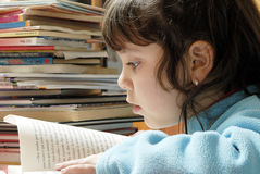 Small girl reading. Over a table surrounded by books stock photo