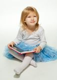 Small girl reading a book and smiling Royalty Free Stock Photo