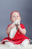 Small girl in  red dress holding shoe Royalty Free Stock Photography