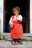 Small girl in red dress, house in mountain, Nepal Royalty Free Stock Photos