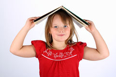 Small girl in red holding a book on her head. Small girl in red clothes smiles white standing with a hardback book on her head Stock Image