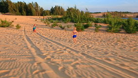 Small Girl Runs Barefooted on Sand Dunes to Mother at Sunset stock video