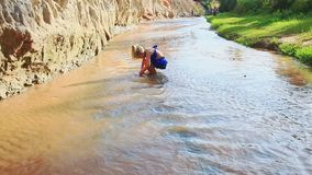 Small girl runs plays in stream shallow water stock footage