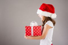 Small girl in santa hat with christmas gift Stock Image