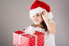 Small girl in santa hat with christmas gift Stock Photography