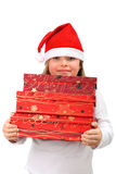 Small girl in Santa's hat carrying three presents Stock Photography