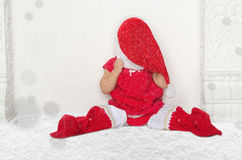Small girl in Santa suit sitting on floor with snow Stock Image