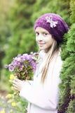 Small girl with seasonal flowers Stock Photos