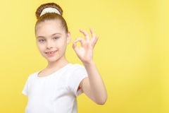 Small girl showing different emotions. Portrait of a small pretty girl showing ok sign with her hand and smiling wearing a white t-shirt with big bun hairstyle Royalty Free Stock Photo