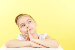 Small girl showing different emotions. Portrait of a small pretty girl thinking of something pleasant and smiling holding her hand near her face wearing a white stock photo