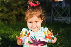 Small girl shows painted colorful hands Royalty Free Stock Images