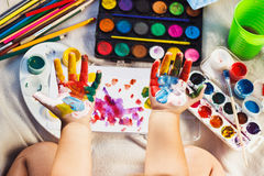 Small girl shows painted colorful hands Royalty Free Stock Photo