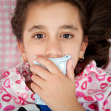 Small girl sick with the flu covering her mouth Stock Photo