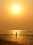 A small girl silhouetted against sun set. At beach area during evening time Royalty Free Stock Photos