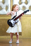 A small girl sings and plays guitar Royalty Free Stock Images