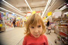 Small girl sit in shoppingcart in supermarket Royalty Free Stock Images
