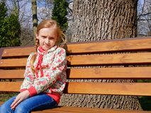 Small girl sits on the bench Royalty Free Stock Photography