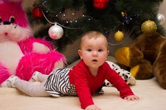 A very small girl sits under a Christmas tree with colorful decorations. New Year and Christmas tree. Small girl sits with Christmas tree. Colored lights and Royalty Free Stock Photography